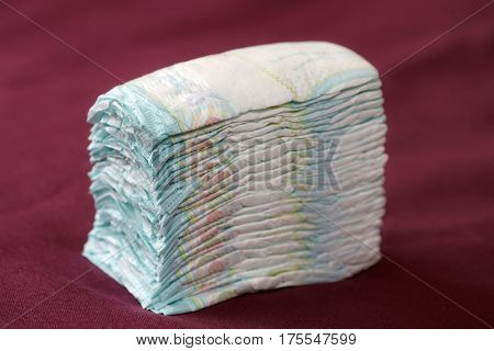 Stack of diapers or nappies on purple background closeup