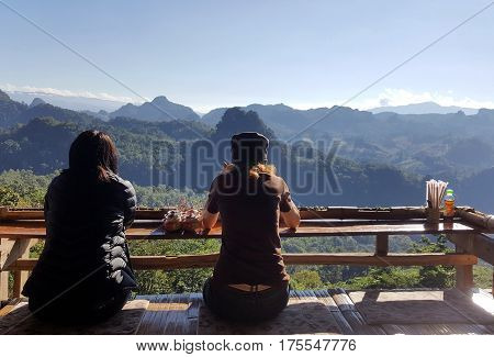 Two women relaxing at view point in the noodle shop at ban ja bo Mae Hong Son Thailand