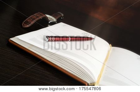 Opening the daily log with pages without records lies on a table. On a notebook the ball-point pen lies. Nearby the watch lies. Horizontal format. Small depth of sharpness. Indoors. Color. Photo.