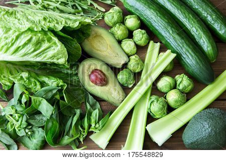 Products containing folic acid - B9 vitamin . Green vegetables on dark wooden background. Celery, arugula, avocado, Brussels sprouts, basil, cucumber romaine salad. space for text