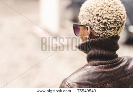 Black woman with short blond afro hair wearing glasses