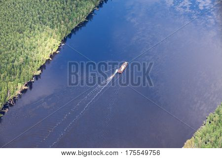 The tug ship and barge with a load moving on the full-flowing river during spring, view from above