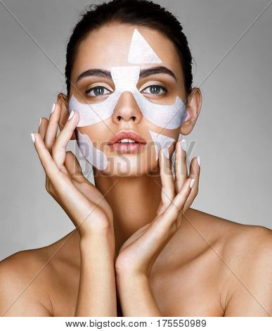 Beautiful brunette woman with cotton facial mask. Portrait of young woman touching hands her face. Skin care concept.
