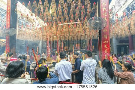 Ho Chi Minh City, Vietnam - January 28th, 2017: Pilgrims pagoda Lunar New Year's Day with hundreds of people holding bouquet of incense tingle slave to pray for peace in the temple joyful atmosphere, the first day bustle in Ho Chi Minh City, Vietnam