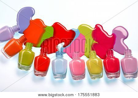 The nail varnish. Photo of spilled from many bottles colorful nail polish on white background. Close up