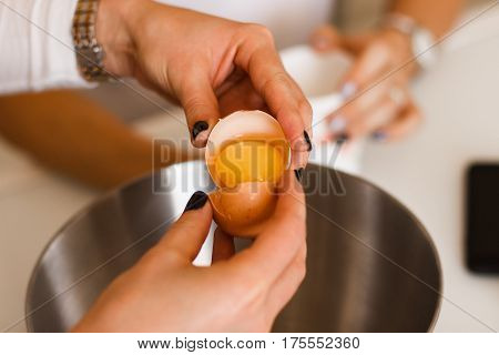 Hand break an egg and pouring into bowl. Key ingredient for tasty omelet and separates albumen from yolk. Ingredient for high-protein dish..