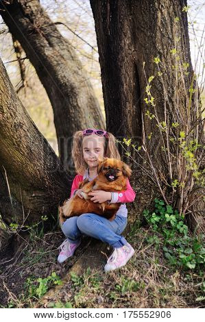 Baby girl with a pekinese sitting on the grass under a large tree