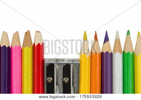 Blunt and sharp colored pencils with sharpener are standing in a row