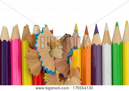 Blunt of sharp colored pencils with wood shavings are standing in a row