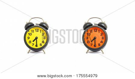 Closeup yellow alarm clock and orange alarm clock for decorate show a half past seven or 7:30 a.m. isolated on white background