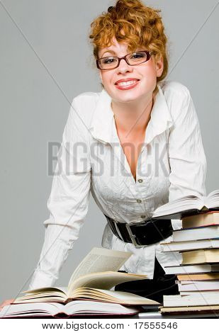 Young pretty woman with eyeglasses over table with books