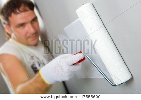 Cheerful worker painting a wall with roller