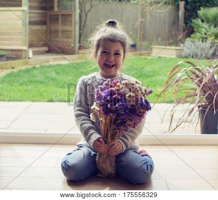 Little Girl Sitting On The Floor Holding Flower