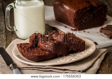 Chocolate-banana Loaf cake on paper  on wooden background