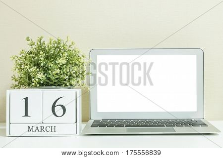 White wooden calendar with black 16 march word with white blank space at center of computer notebook on white wood desk and cream wallpaper textured background selective focus at the calendar