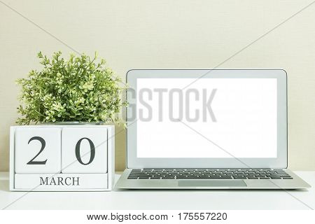 White wooden calendar with black 20 march word with white blank space at center of computer notebook on white wood desk and cream wallpaper textured background selective focus at the calendar