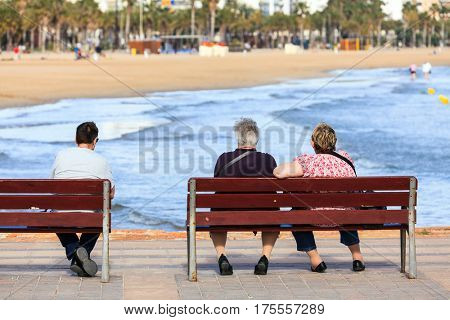 Seniors sitting and on the benches in front of the ocean or sea