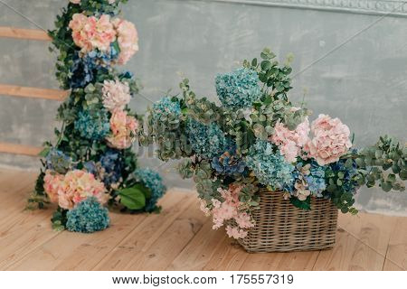 On the wooden floor a beautiful bouquet of hydrangeas in a large wicker basket and flower garland.