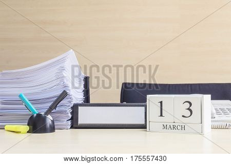 Closeup white wooden calendar with black 13 march word on blurred brown wood desk and wood wall textured background in office room view with copy space selective focus at the calendar