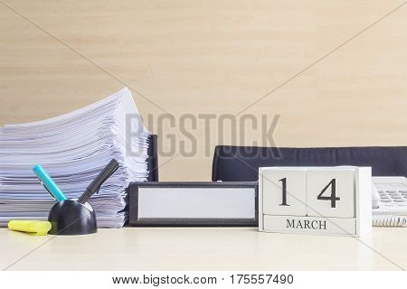 Closeup white wooden calendar with black 14 march word on blurred brown wood desk and wood wall textured background in office room view with copy space selective focus at the calendar