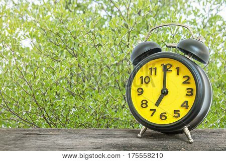 Closeup black and yellow alarm clock for decorate in 7 o'clock on old brown wood desk on green leaves in the park textured background