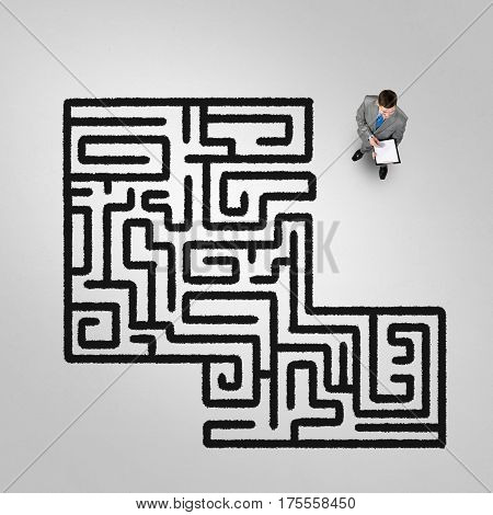 Top view of puzzled businessman looking at drawn maze on floor