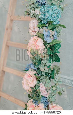 On a wooden staircase a delicate lush floral garland of hydrangea
