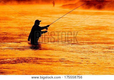Man flyfishing in misty river in the morning light
