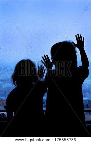 Rainy Day with little girls at window looking out wanting to play