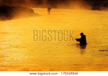 Silhouette of Man Flyfishing Fishing in River