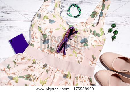 Woman stylish summer clothing - floral beige dress, leather nude shoes, violet smartphone, violet sunglasses, jewellery