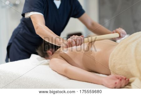 Masseur Using Massage Bamboo Sticks