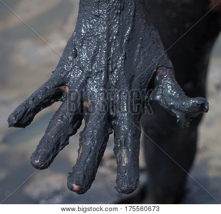 Woman's hand smeared with black healing mud.