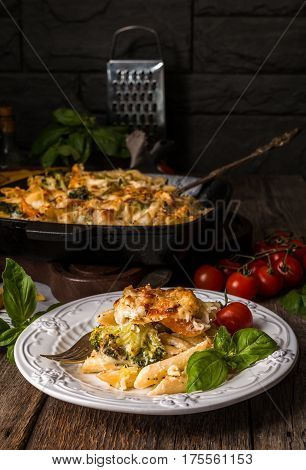 Baked pasta with broccoli, cauliflower, cheese and bechamel sauce in a white plate on wooden background