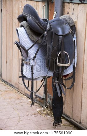 Leather sport saddle hanging in the stable for equestrian sport