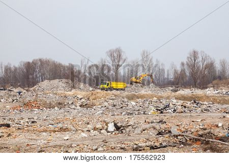 City landfill. Truck and excavator working at a distance.