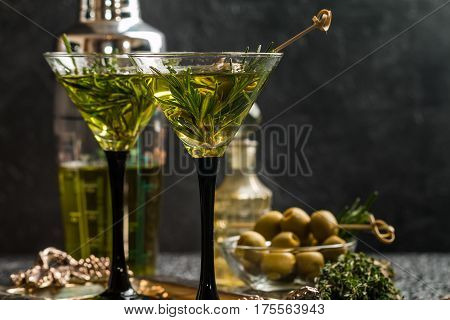 Two fresh green cocktails with rosemary and olives in martini glasses on gray background