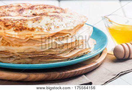 Stack of yeast pancakes, traditional for Russian pancake week witn honey