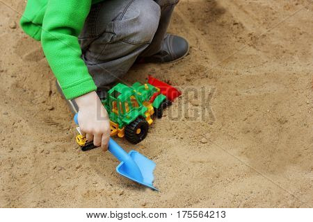 Walks for children in the fresh air. Part of the image of a small child who sits in the sandbox and playing with toy construction vehicles with a shovel.
