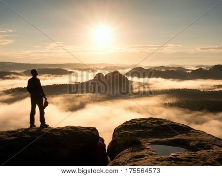 Hiker Silhouette Standing On Rocky Summit Above Misty Valley.