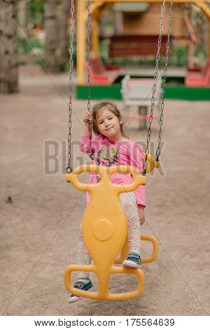 Summer sunny day sweet girl riding on a swing in the playground