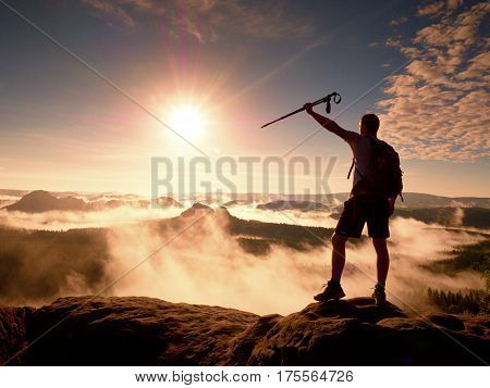 Tall backpacker with poles in hand. Sunny misty daybreak in rocky mountains. Hiker with backpack stand on rocky view point above valley. Vivid and strong vignetting effect.