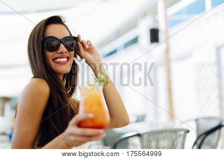 Sexy woman drinking cocktail in summer and enjoying her vacation