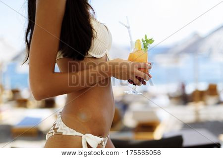 Sexy young woman holding cocktail on beach