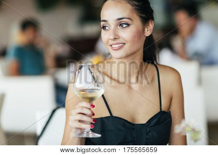 Woman Tasting White Wine In Restaurant