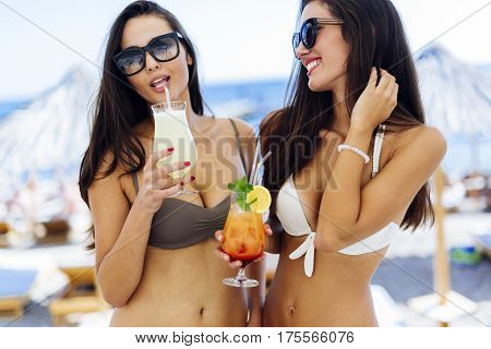 Beautiful sexy women sipping cocktails on beach