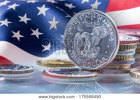 Dollar coins and USA flag in the background. USA Dollar coins standing on edge supported on coins