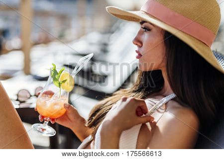 Stunning Woman Holding Cocktail While Sunbathing
