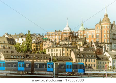 Metro train in foreground and old architecture of Stockholm in background. Sweden Scandinavia Europe