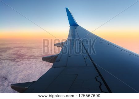View at the aeroplane wing at the sunset over clouds